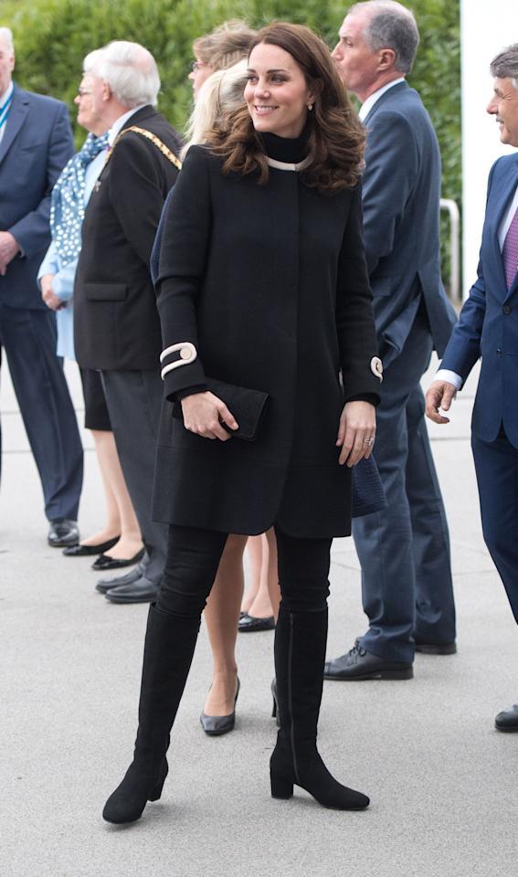 <p>Middleton wears a black and white coat by Goat Fashion, skinny jeans, a black clutch, and knee-high boots during a visit to Birmingham, England. </p>