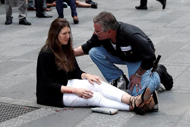 <p>A man helps an injured woman on the sidewalk in Times Square after a speeding vehicle struck pedestrians on the sidewalk in New York City on May 18, 2017. (Mike Segar/Reuters) </p>