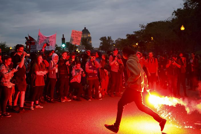 <p>A protester runs with a flare outside the National Assembly of Quebec during a demonstration ahead of the Group of Seven (G7) Leaders' Summit in Quebec City, Quebec, Canada on June 7, 2018. (Photo: Cole Burston/Bloomberg via Getty Images </p>