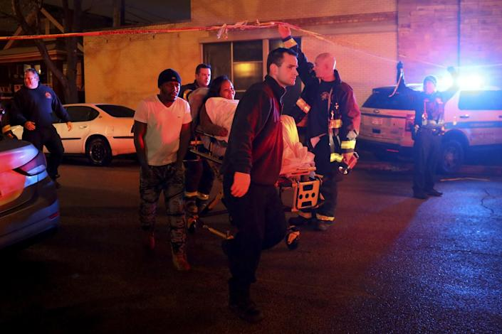 A woman who was shot is taken to an ambulance by members of the Fire Department at the scene where at least six people were shot, one fatally, on the 8600 block of South Maryland Avenue on Dec. 25, 2016 in Chicago. (Photo: Armando L. Sanchez/Chicago Tribune/TNS via Getty Images)