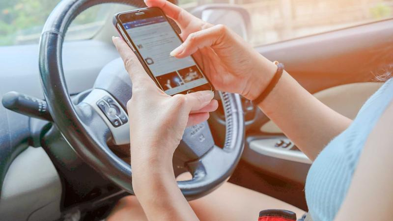 Woman using smartphone with both hands while driving
