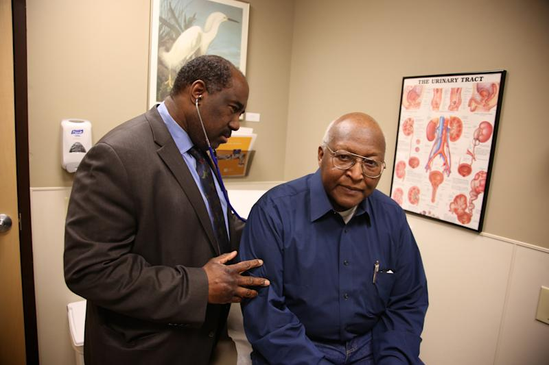 This photo taken Feb. 24, 2014, provided by the Roswell Park Cancer Institute, shows Dr. Willie Underwood, a urologic oncologist at Roswell Park Cancer Institute, examining patient Richard Waldrop at the Roswell Park Cancer Institute, in Buffalo, N.Y. Cancer patients relieved that they can get insurance coverage because of the new health care law may be disappointed to learn that some of the nation's best cancer hospitals are off limits. Only four of 19 nationally recognized comprehensive cancer centers that responded to an Associated Press survey said patients have access through all the insurance companies in their state's exchange, or primary market. (AP Photo/Roswell Park Cancer Institute, Bill Sheff)