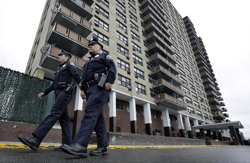 In this Tuesday, April 15, 2014, photograph, Camden County Metro police officers Lucas Murray, left, and Daniel Torres patrol outside the high-rise apartment building, Northgate I, in Camden, N.J. Camden disbanded its police department on May 1 and handed patrols over to the new Camden County-run department that promised more officers for the same cost, largely because it could shed provisions of a union contract that officials saw as onerous. The new department says crime dropped sharply in every category except arson in the first three months of this year, when the new department had enough officers for intense patrols in every neighborhood. (AP Photo/Mel Evans)