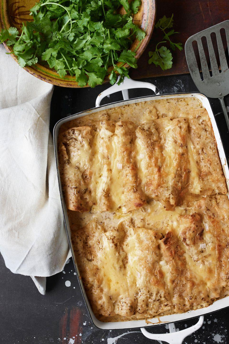 """<p>Take a gander at these cheesy chicken enchiladas. """"To give a kick to my sour cream sauce,"""" the author says, """"I add serrano chiles and tomatillos.""""</p><p><strong><a href=""""https://www.countryliving.com/food-drinks/recipes/a3779/sour-cream-chicken-enchiladas-recipe-clx0312/"""" rel=""""nofollow noopener"""" target=""""_blank"""" data-ylk=""""slk:Get the recipe"""" class=""""link rapid-noclick-resp"""">Get the recipe</a>.</strong></p>"""
