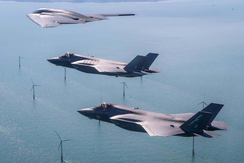 A United States Air Force B2 Spiri flies above the English countryside near Dover with two RAF F-35 jets (MOD)