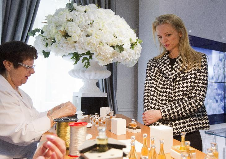 """Assistant general manager Christian Dior Couture Delphine Arnault, right, looks a Dior perfume during his visit of """"Particular operation days"""" in LVMH, the world's largest luxury company at the Fashion House Dior in Paris, Saturday June 15, 2013. (AP Photo/Jacques Brinon)"""