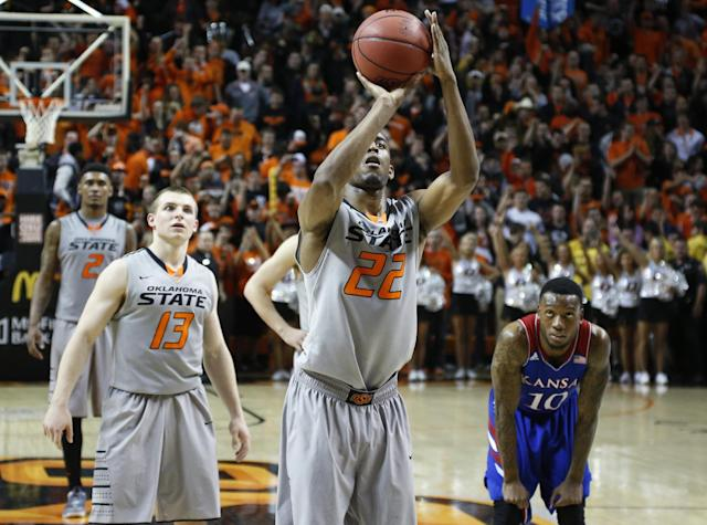 Oklahoma State wing Markel Brown (22) shoots a foul shot in front of teammate Phil Forte (13) and Kansas guard Naadir Tharpe (10) with seconds left in an NCAA college basketball game in Stillwater, Okla., Saturday, March 1, 2014. Oklahoma State won 72-65. (AP Photo/Sue Ogrocki)