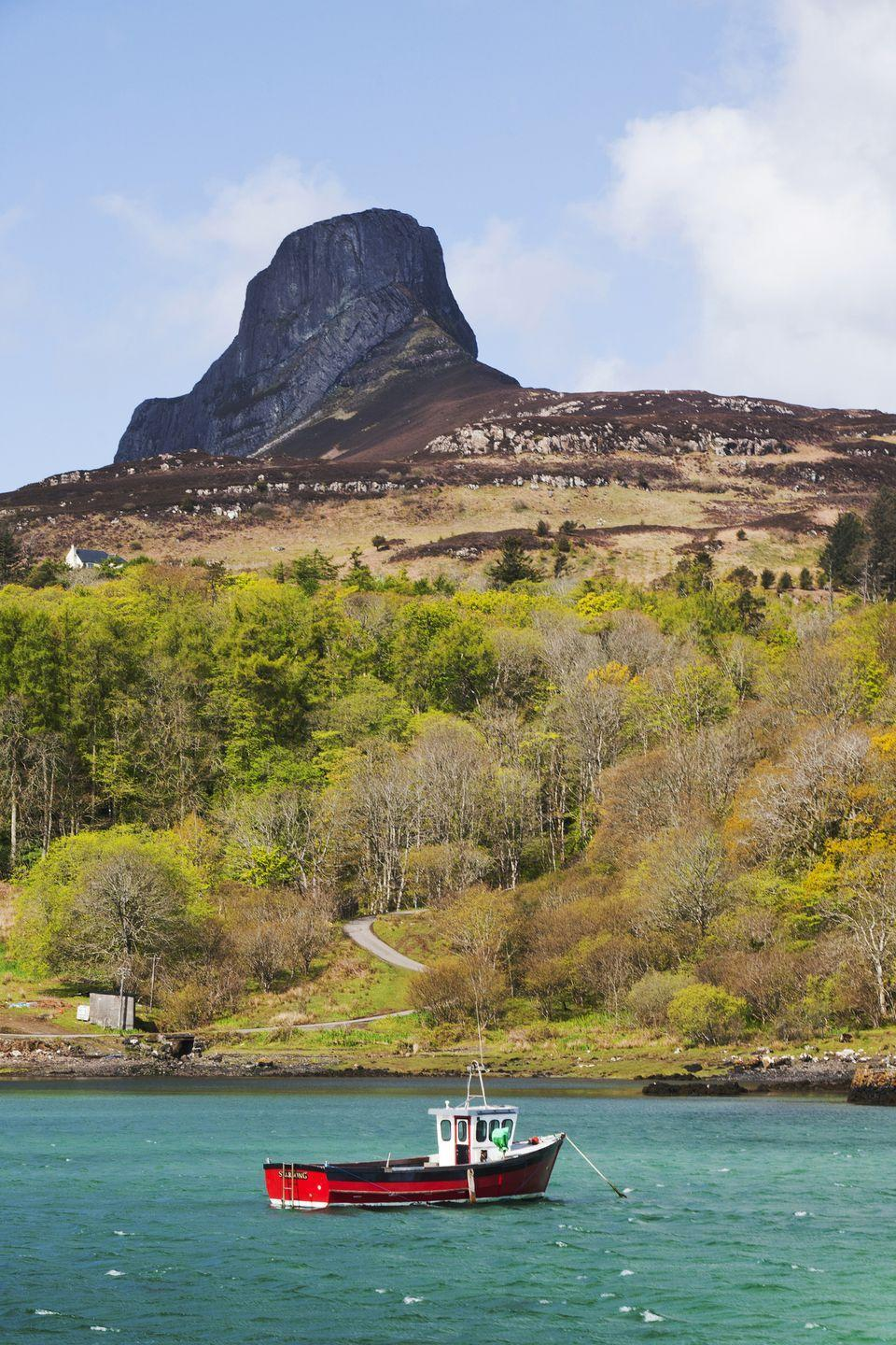 """<p>On the isolated isle of Eigg, An Sgùrr watches over a wild and windswept landscape. Formed more than 58 million years ago – when a volcanic eruption sent lava spilling into a deep river valley – this pitchstone peak is the largest of its kind in Europe. While it might appear scarily steep at a glance, the scramble to the summit isn't a strenuous one. Follow a well-marked path, past the red-roofed farmhouse at Galmisdale and an abandoned settlement at Grulin, to the top for sprawling views over lonely lochs and out to the distant pinnacles of Skye.</p><p><a class=""""link rapid-noclick-resp"""" href=""""https://www.walkhighlands.co.uk/"""" rel=""""nofollow noopener"""" target=""""_blank"""" data-ylk=""""slk:MORE INFO"""">MORE INFO</a></p>"""