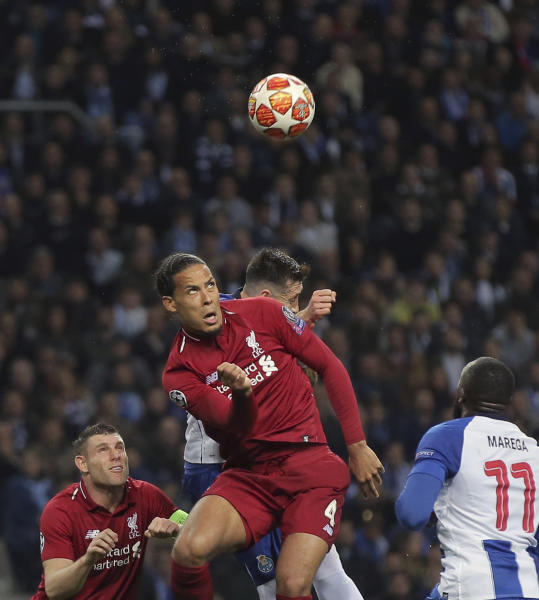 Liverpool's Virgil van Dijk, center, heads the ball the Champions League quarterfinals, 2nd leg, soccer match between FC Porto and Liverpool at the Dragao stadium in Porto, Portugal, Wednesday, April 17, 2019. (AP Photo/Luis Vieira)