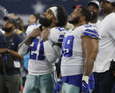 Dallas Cowboys running back Ezekiel Elliott (21) and nose tackle Antwaun Woods (99) look at the scoreboard in the second half of an NFL football game against the Jacksonville Jaguars in Arlington, Texas, Sunday, Oct. 14, 2018. (AP Photo/Ron Jenkins)