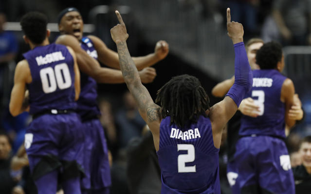 Kansas State players celebrate a win over Kentucky after a regional semifinal NCAA college basketball tournament game, Friday, March 23, 2018, in Atlanta. Kansas State won 61-58. (AP Photo/David Goldman)
