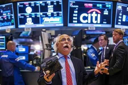 FILE PHOTO: Trader Tuchman gestures as he talks on the phone following the resumption of trading following a several hour long stoppage on the floor of the New York Stock Exchange