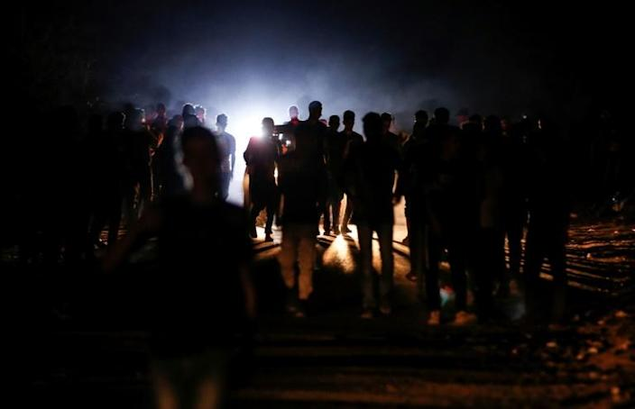 """Palestinian protesters from a group calling themselves the """"Night Confusion Units"""" gather near the Gaza-Israel border east of al-Bureij camp for Palestinian refugees in the central Gaza Strip on Sunday"""