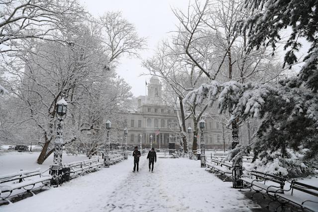 <p>Pedestrians walk through the park at City Hall in New York City as a spring storm hit the Northeast with strong winds and a foot or more of snow expected in some parts of the region on Wednesday, March 21, 2018. (Photo: Gordon Donovan/Yahoo News) </p>