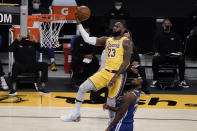 Los Angeles Lakers' LeBron James, top, goes up for a basket as Golden State Warriors' Andrew Wiggins watches during the first half of an NBA basketball game, Monday, Jan. 18, 2021, in Los Angeles. (AP Photo/Jae C. Hong)