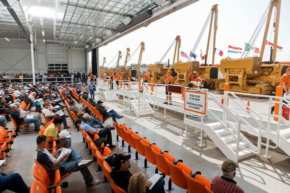 Heavy equipment on display in front of row of auction participations