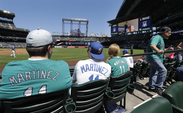 Seattle Mariners fans watch a monitor showing former Mariners' designated hitter Edgar Martinez as he speaks during his Hall of Fame induction ceremony before a baseball game Sunday, July 21, 2019, in Seattle. (AP Photo/Elaine Thompson)