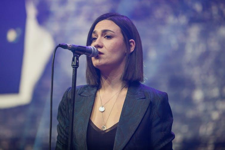 Musician Nadine Shah singing into microphone.