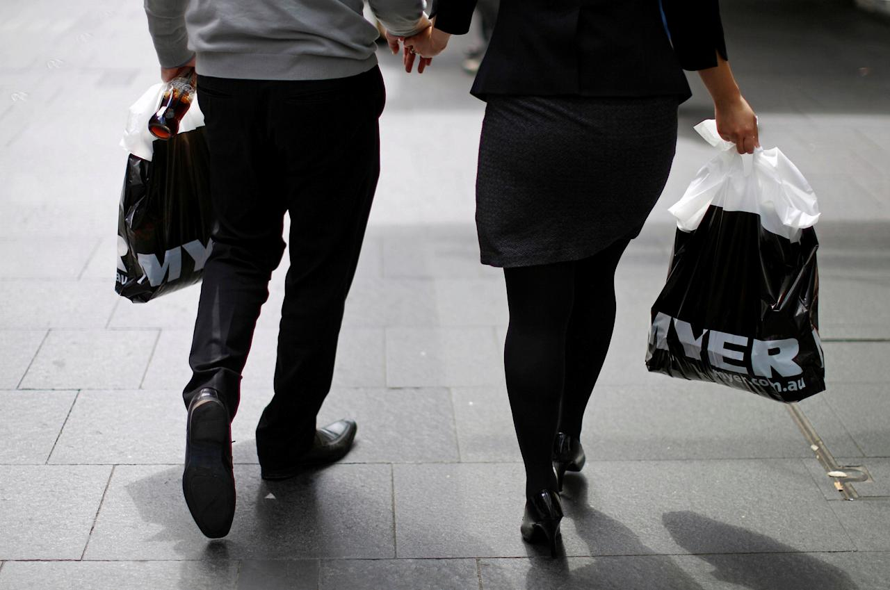 FILE PHOTO - A couple hold hands as they walk with bags containing their shopping from retailer Myer Holdings Ltd in central Sydney, Australia, March 6, 2014.  REUTERS/Jason Reed/File Photo