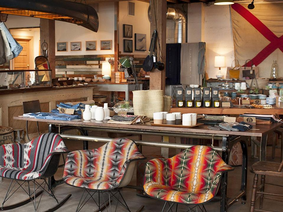 """<p><strong>What's the story with this shop?</strong><br> Owned and run by husband-wife team Jocelyn and Robert Rahm, this lovingly renovated 7000-square-foot former industrial warehouse turned design showroom is exactly what you'd imagine a Portland home decor haven should be, with raw concrete floors covered in soft Navajo rugs, white-washed brick and warm wood walls, and ceiling beams strung with delicate bundles of dried flowers. Long, low slung leather sofas slung with lush pelts and vintage wool blankets are arranged around coffee tables sweetly dotted with Shel Silverstein poetry books, earthy ceramic bowls, and sticks of fragrant copal incense, all conspiring to create what is essentially the living room of your dreams. Before pivoting into retail and woodworking, Jocelyn worked in education and Robert was a counselor for at-risk youth, hence the warm and genuine vibes you'll feel from the moment you're welcomed into the shop until you reluctantly leave.</p> <p><strong>What can we find here, or what should we look for?</strong><br> Start by the front door, wondering if you do in fact need a pink and gold pyramid jute doormat (yes), wander down the wall coveting the fragrant little Saint Rita Parlor roll-on perfumes and jars of <a href=""""https://www.cntraveler.com/stories/2016-08-02/why-washingtons-orcas-island-should-be-your-next-family-getaway?mbid=synd_yahoo_rss"""" rel=""""nofollow noopener"""" target=""""_blank"""" data-ylk=""""slk:Orcas Island"""" class=""""link rapid-noclick-resp"""">Orcas Island</a>-based Ula's sea buckthorn beauty balm, try and remember if anyone you know is having a baby sometime soon so you can justify splurging on pair of itty bitty Nico Nico striped cotton overalls, take a mental picture of the center of the store so that you can recreate the same effortlessly gorgeous leather sofa-coffee table-Navajo rug configuration at home, contemplate switching your entire wardrobe to silky soft hemp Jungmaven t-shirts and sweatshirts and Atolyia's hooded Turkish cotton"""