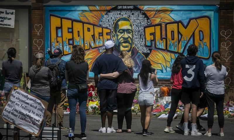 Mourners at a mural of George Floyd, close to the spot where he died in Minneapolis.