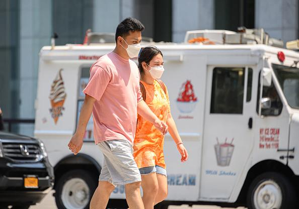 People wear protective face masks near an ice cream truck on Fifth Avenue as the city enters Phase 4 of re-opening following restrictions imposed to slow the spread of coronavirus in New York City.