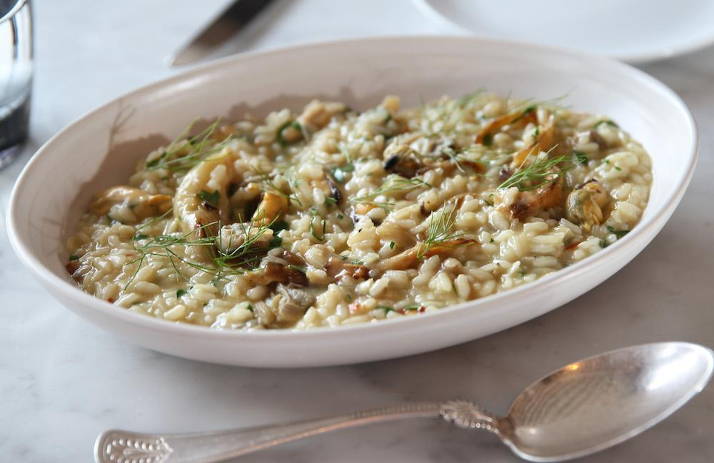 "<p>Plenty of risotto recipes include a glass or two of wine. I read somewhere that it helps dissolve alcohol soluble flavour compounds and release them into the dish so, hey, you could end up with a tastier risotto. Try <a rel=""nofollow"" href=""http://www.jamieoliver.com/recipes/rice-recipes/a-basic-risotto-recipe/"">this recipe from Jamie Oliver</a>. [Photo: Getty} </p>"