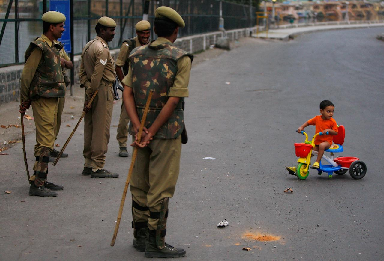 SRINAGAR, INDIA - OCTOBER 5: Indian security forces stand guard during a curfew watching a child ride his tricycle October 5, 2008 in Srinagar, Kashmir, India. A strict curfew in Indian Kashmir was imposed starting today as thousands of troops have been deployed to prevent a major pro-independence rally from taking place on Monday. The curfew includes all Muslim towns within Indian Kashmir. Separatist leaders have also been detained. Kashmiri people have been protesting against Indian rule claiming that they are alienated from the Indian state and want a platform for autonomy.  (Photo Paula Bronstein/Getty Images)