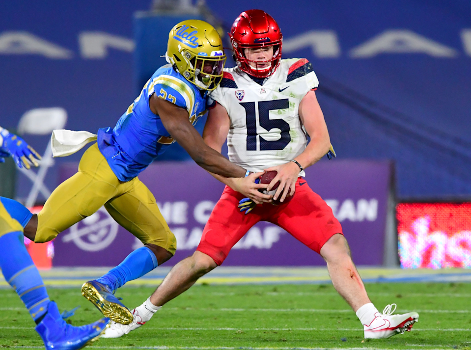 UCLA defensive back Obi Eboh strips the ball from Arizona quarterback Will Plummer