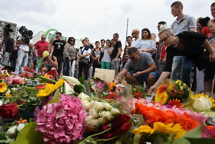 People lay flowers for the victims of the shooting near the Olympia-Einkaufszentrum shopping centre in Munich, southern Germany, on July 23, 2016, a day after the attack (AFP Photo/Christof Stache)