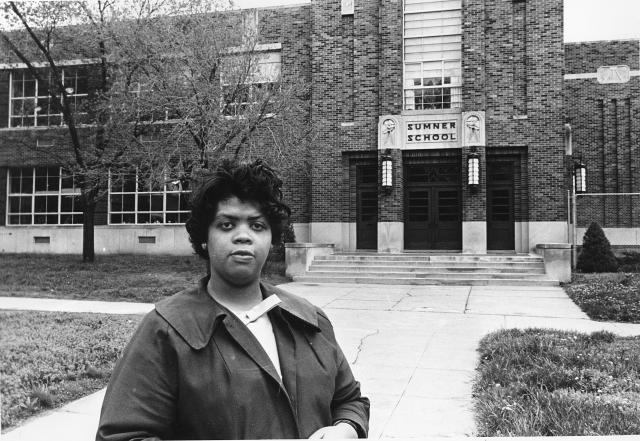 """Linda Brown Smith stands in front of the Sumner School in Topeka, Kan., on May 8, 1964. The refusal of the public school to admit Brown in 1951, then nine years old, because she is black, led to the Brown v. Board of Education of Topeka, Kansas. In 1954, the U.S. Supreme Court overruled the """"separate but equal"""" clause and mandated that schools nationwide must be desegregated. (AP Photo)"""