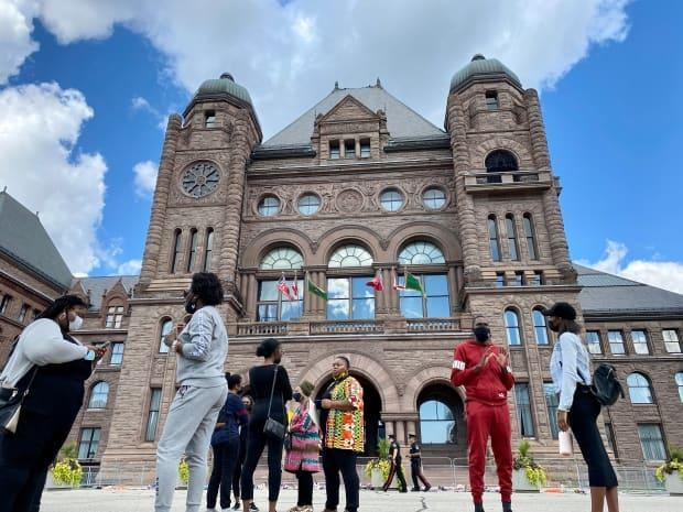 The launch event for the new advocate program was held in front of Queen's Park on Friday. Patricia Falope stands in the centre of the image, wearing orange, yellow and green.  (Jessica Ng/CBC - image credit)