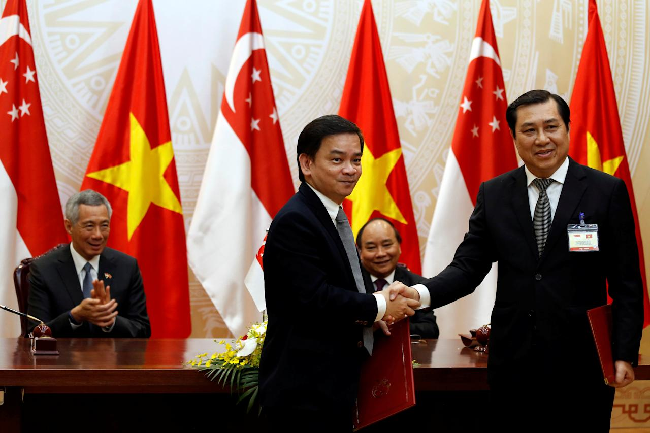 Chairman of Da Nang People's Committee Huynh Duc Tho (R) shakes hands with Sembcorp CEO Kelvin Teo as Singapore's Prime Minister Lee Hsien Loong (L) and Vietnam's Prime Minister Nguyen Xuan Phuc (2nd R) look on during a signing ceremony in Hanoi, Vietnam March 23, 2017.  REUTERS/Kham