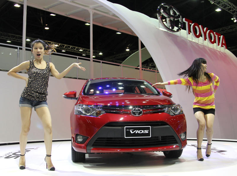 FILE - In this Tuesday, March 26, 2013 file photo, Thai dancers introduce a brand-new compact sedan Toyota Vios on the press day of the Bangkok Motor Show in Bangkok, Thailand. Toyota Motor Corp. held onto its status as the world's top-selling automaker in the first quarter of this year, although the three-way race with General Motors and Volkswagen is proving tight, as its sales fall in China and Japan. Toyota reported Wednesday, April 24, it sold 2.43 million vehicles during the January-March period, outpacing U.S. automaker General Motors Co. at 2.36 million vehicles and Volkswagen AG of Germany at 2.27 million vehicles. (AP Photo/Sakchai Lalit, File)