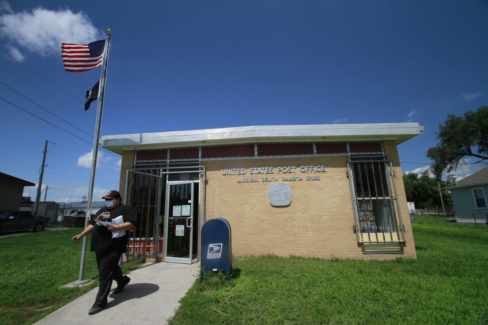 The post office in Mission, S.D. saw a steady flow of people on Aug. 6, 2020. The post office is one of four on the roughly 2,000 square miles (5,180 square kilometers) of the Rosebud Indian Reservation (AP Photo/Stephen Groves)