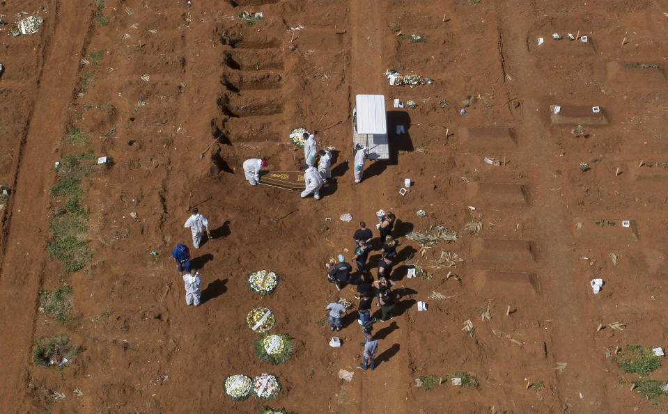 Cemetery workers in full protective gear carry a coffin that contains the remains of a person who died from complications related to COVID-19 at the Vila Formosa cemetery in Sao Paulo, Brazil, Wednesday, March 24, 2021. (AP Photo/Andre Penner)