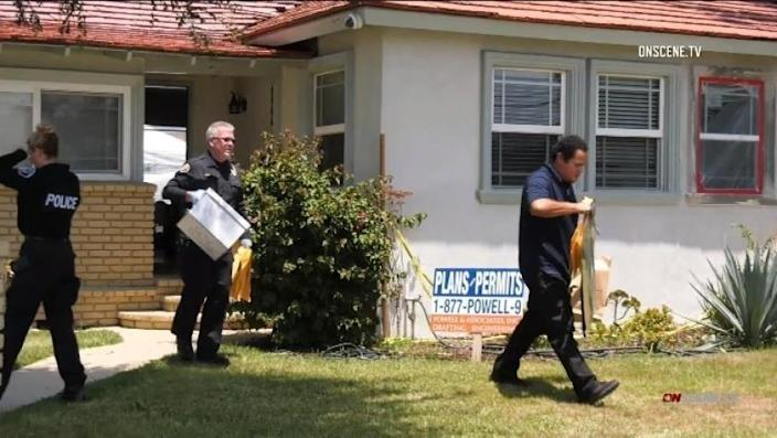 Investigators remove evidence from a home in Downey after arresting a man Thursday on suspicion of animal cruelty.