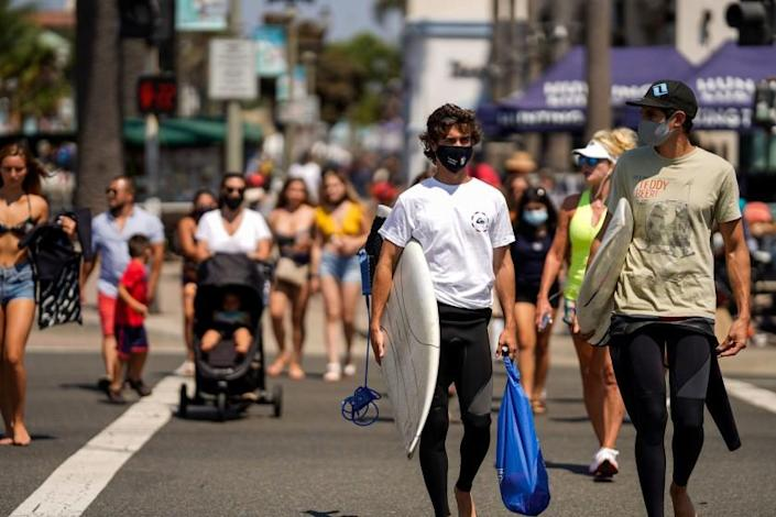 HUNTINGTON BEACH, CA - SEPTEMBER 04: Surfers wearing face coverings cross the street towards the Huntington Beach Pier, on Friday, Sept. 4, 2020 in Huntington Beach, CA. As California braces for a looming heatwave Gov. Gavin Newsom issued an emergency proclamation aimed at shoring up the state's energy capacity with scorching temperatures being set to sear the state through the Labor Day weekend. (Kent Nishimura / Los Angeles Times)