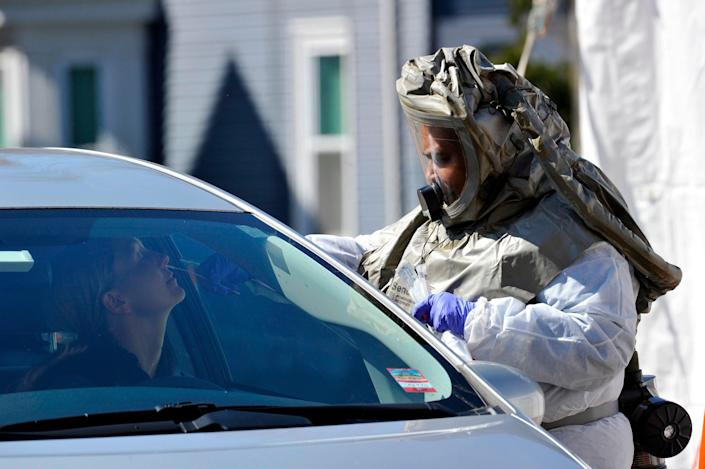 A nurse in a hazmat suit swabs a woman's nose during a test for coronavirus at Somerville Hospital in Massachusetts.
