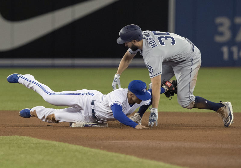 San Diego Padres' Eric Hosmer is out at second base trying to stretch a single into a double as Toronto Blue Jays second baseman Cavan Biggio makes the tag in the fourth inning of their baseball game in Toronto, Sunday, May 26, 2019. (Fred Thornhill/The Canadian Press via AP)