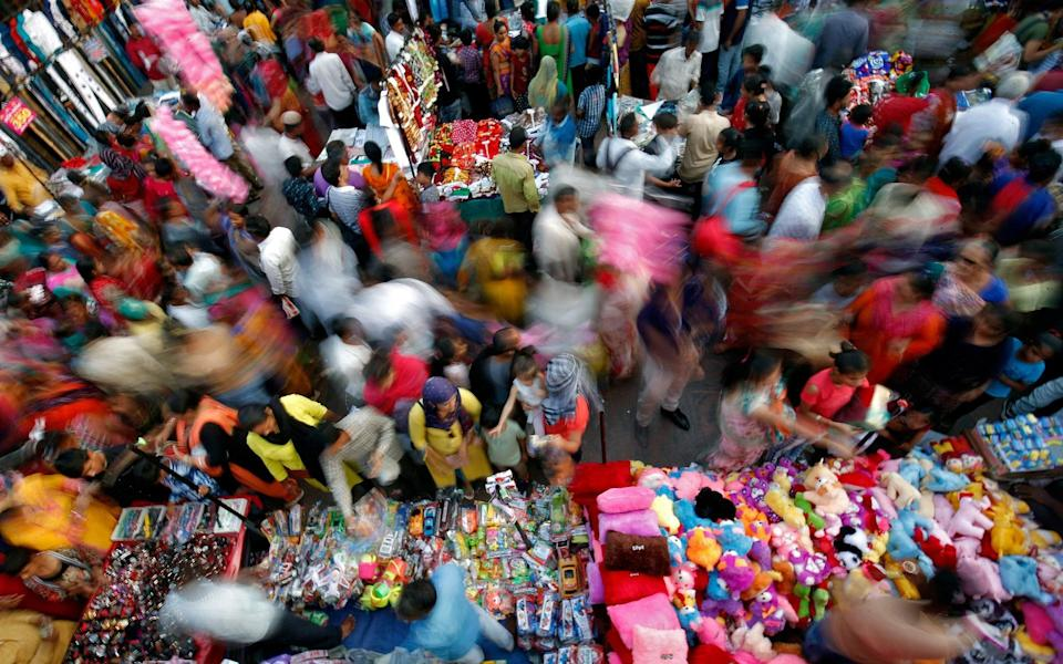 Shoppers at a busy market in Ahmedabad - Reuters