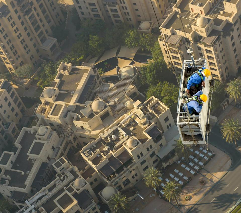 Two laid-back workmen were spotted hanging by two wires from one of the city's tallest skyscrapers as they went about their daily business. The palm-sweating images were taken by Zohaib Anjum at the Address Downtown building in Dubai. (SWNS)