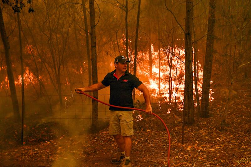Firefighters hose down during a bushfire in Werombi, 50km southwest of Sydney.