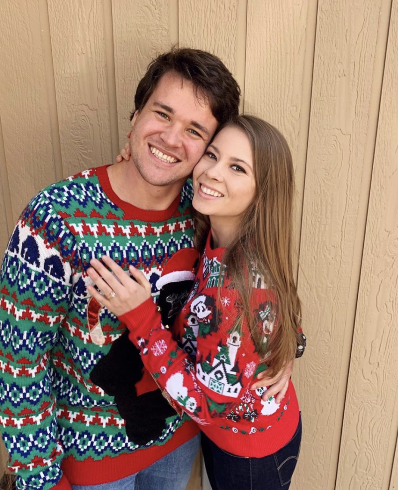 Bindi Irwin and Chandler Powell wearing Christmas-themed jumpers.