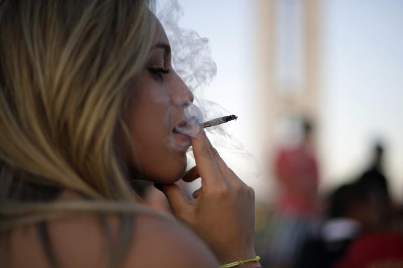 A demonstrator smokes a giant cannabis cigarette during a pro-marijuana legalization march in Brasilia