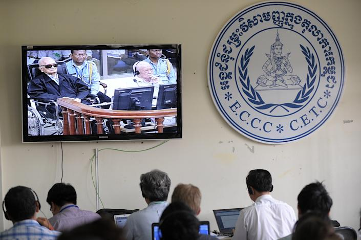 """Journalists watch a live video feed of """"Brother Number Two"""" Nuon Chea (L) and former Khmer Rouge head of state Khieu Samphan in the courtroom during their trial at the Extraordinary Chamber in the Courts of Cambodia in Phnom Penh on August 7, 2014 (AFP Photo/Tang Chhin Sothy)"""