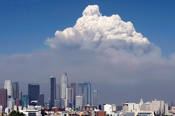 A large cloud with dark smoke rises in the background behind the downtown Los Angeles skyline