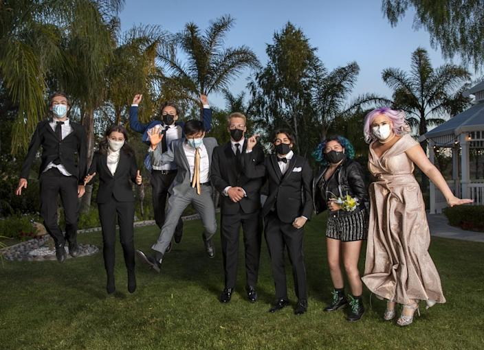 Seniors in formal attire and masks stand, some jump in the air.