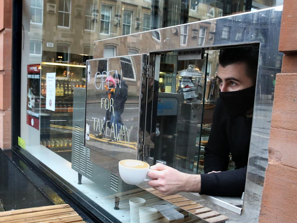 <p>A member of staff looks out from a serving hatch at the Tinderbox coffee shop in Glasgow, as stricter lockdown measures have came into force for mainland Scotland</p> (PA)