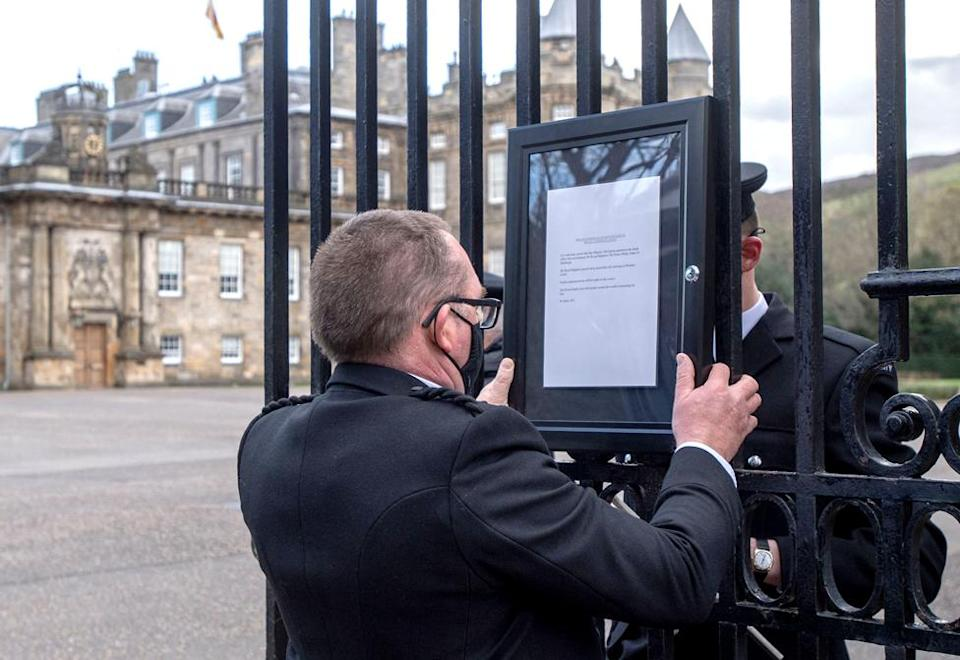A member of staff attaches a notice to the gates of the Palace of Holyrood house in Edinburgh
